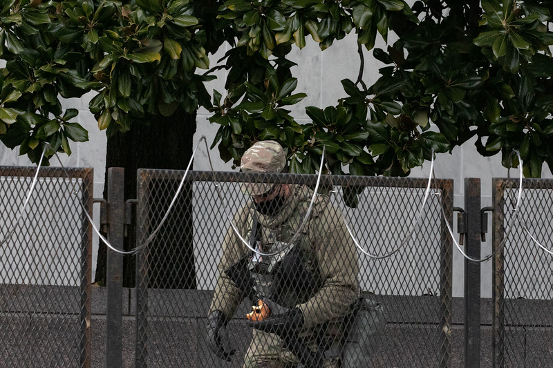 A National Guard member eats a donut given to him by a resident as a gesture of gratitude for his service