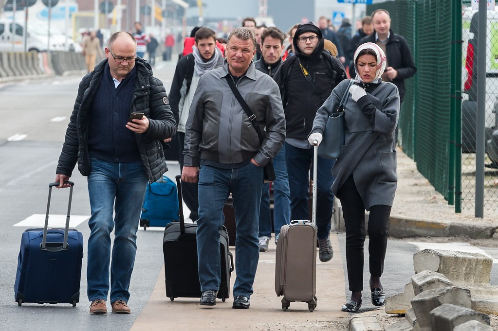 . People walk away from Brussels airport after explosions rocked the facility in Brussels, Belgium Tuesday March 22, 2016.   Explosions rocked the Brussels airport and the subway system Tuesday, just days after the main suspect in the November Paris attacks was arrested in the city, police said. (AP Photo/Geert Vanden Wijngaert)