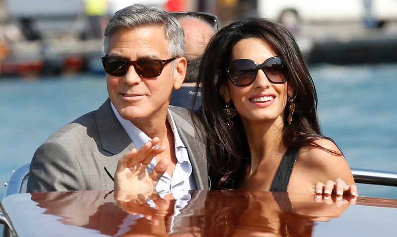 . George Clooney, left, and Amal Alamuddin arrive in Venice, Italy, Friday, Sept. 26, 2014. Clooney, 53, and Alamuddin, 36, are expected to get married this weekend in Venice, one of the worldís most romantic settings. (AP Photo/Luca Bruno)