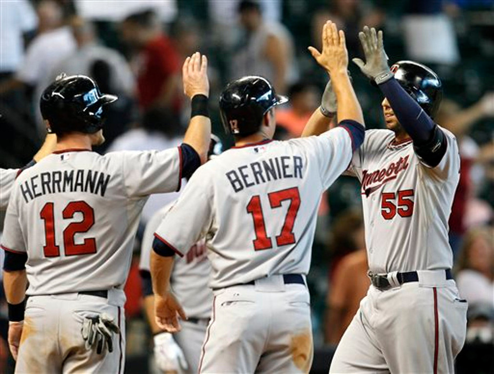 . Minnesota Twins\' Chris Colabello (receives high-fives from Doug Bernier and Chris Herrmann  after hitting a grand slam home run against the Houston Astros in the ninth inning.  (AP Photo/Bob Levey)