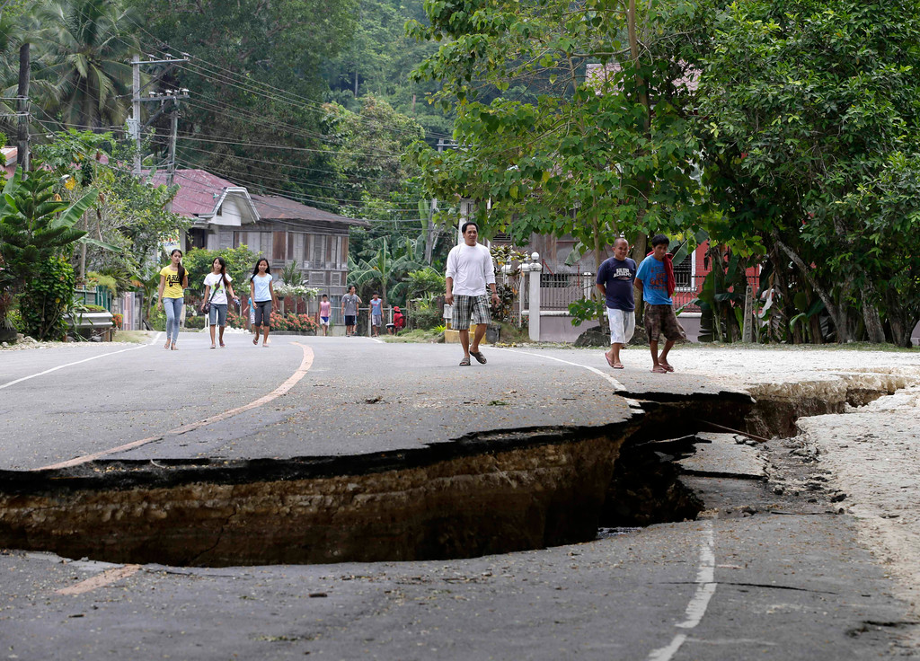 . Residents walk on a damaged highway in Loboc township, Bohol province in central Philippines Wednesday Oct. 16, 2013, a day after a 7.2-magnitude quake hit Bohol and Cebu provinces.  (AP Photo/Bullit Marquez)