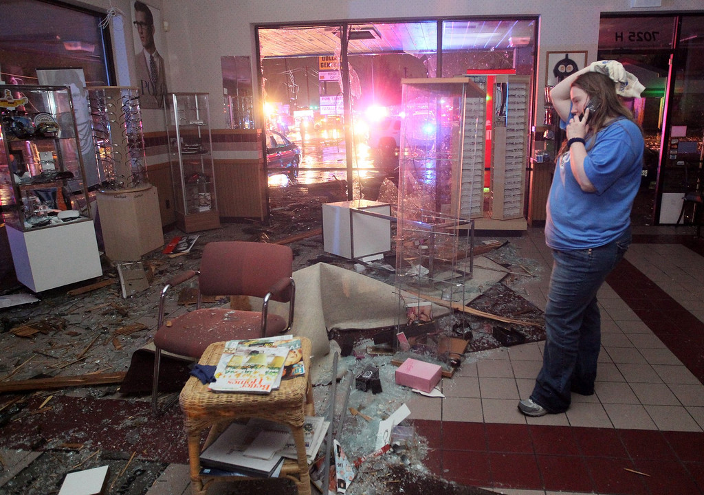 """. Kristin Little, manager of the Ferguson Optical shop in Hazelwood, talks with a friend on the phone as she describes the damage caused to her shop by a storm on Wednesday, April 10, 2013. Butch Dye, a hydrometeorological technician with the National Weather Service in St. Louis, Mo., said severe weather struck the suburb of Hazelwood.  \""""We won\'t be able to confirm whether it was a tornado until teams get out there tomorrow,\"""" Dye said. (AP Photo/David Carson, Post-Dispatch)"""