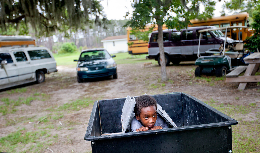 . Jermarkest Wilson, 7, plays in a cart in the backyard of his home on Sapelo Island, Ga. on Sunday, June 9, 2013. Eight children catch a ferry every morning to attend school on the mainland since the last school operating on the island closed in 1978. (AP Photo/David Goldman) PART OF A 35-PICTURE ESSAY BY DAVID GOLDMAN
