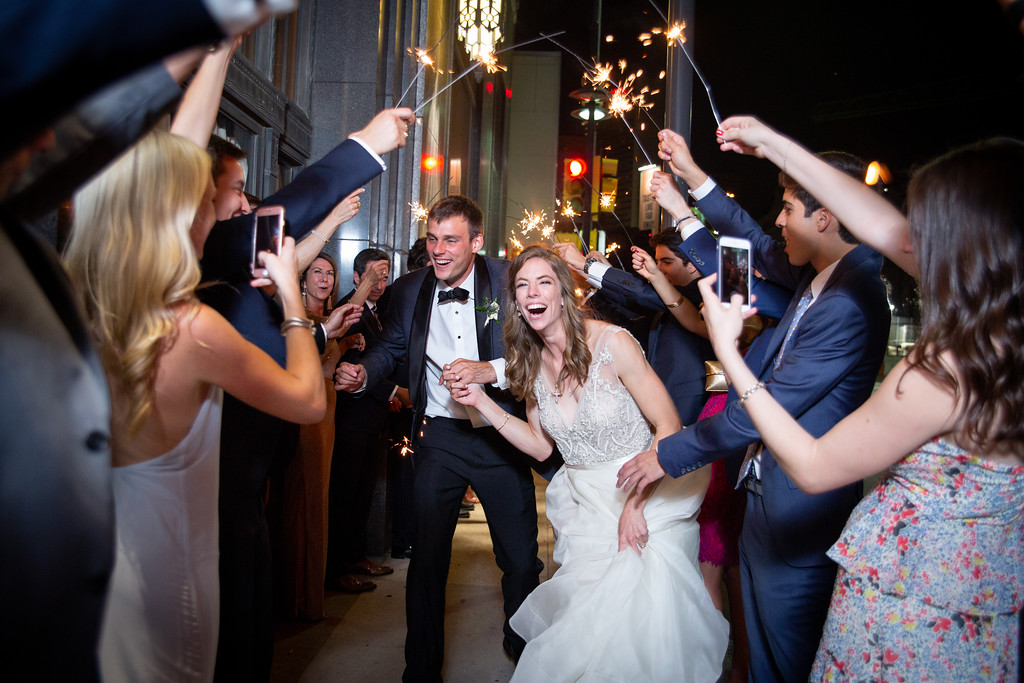 bride and groom exit their wedding with a grand exit as sparklers are waved by their wedding guests