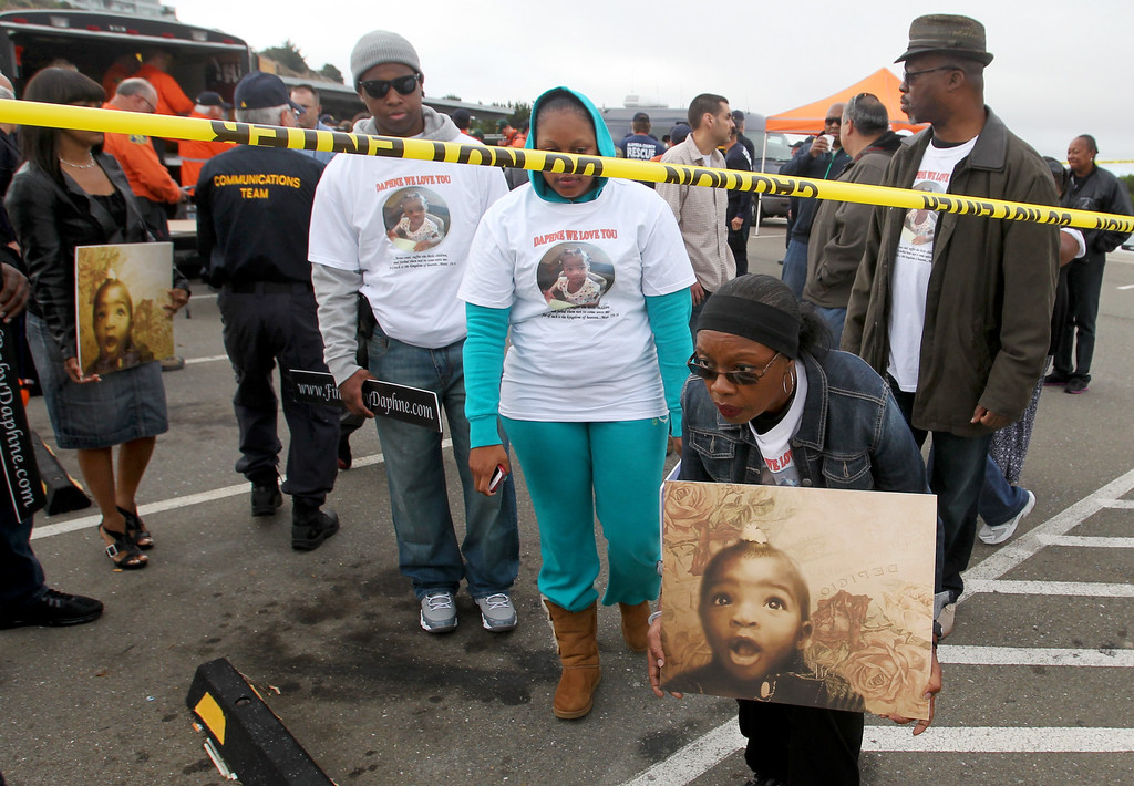 . Evelyn Williams, center, of Vallejo, carries a photo of her missing cousin 22-month-old Daphne Webb, as she\'s followed by family members, while Oakland police, along with Alameda County Sheriff and Santa Clara County Sheriff volunteer rescue teams and FBI agencies, begin the search for the missing child near Merritt College in Oakland, Calif., on Saturday, Aug. 24, 2013. (Ray Chavez/Bay Area News Group)