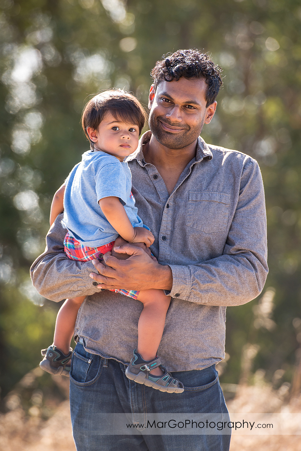 portrait of father holding little boy in blue shirt looking into camera at Richmond Marine View