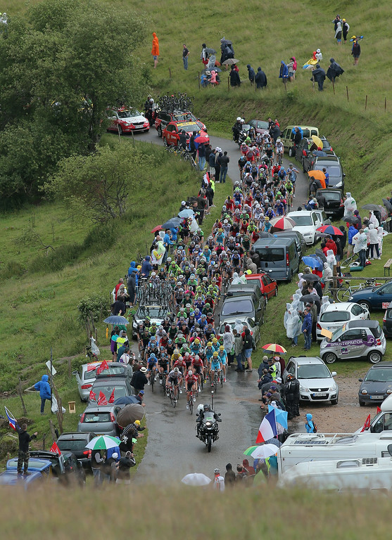 . The peloton makes the climb of the Petit Ballon as fans shelter themselves from the rain during stage ten of the 2014 Le Tour de France from Mulhouse to La Planche des Belles Filles on July 14, 2014 in Munster, France.  (Photo by Doug Pensinger/Getty Images)