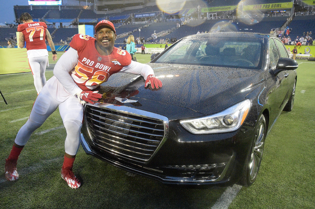 . AFC linebacker Von Miller (58), of the Denver Broncos, poses with the car he won for winning the MVP Defensive Player of the Game, at the NFL Pro Bowl football game, Sunday, Jan. 28, 2018, in Orlando, Fla. The AFC defeated the NFC 24-23. (AP Photo/Phelan M. Ebenhack)