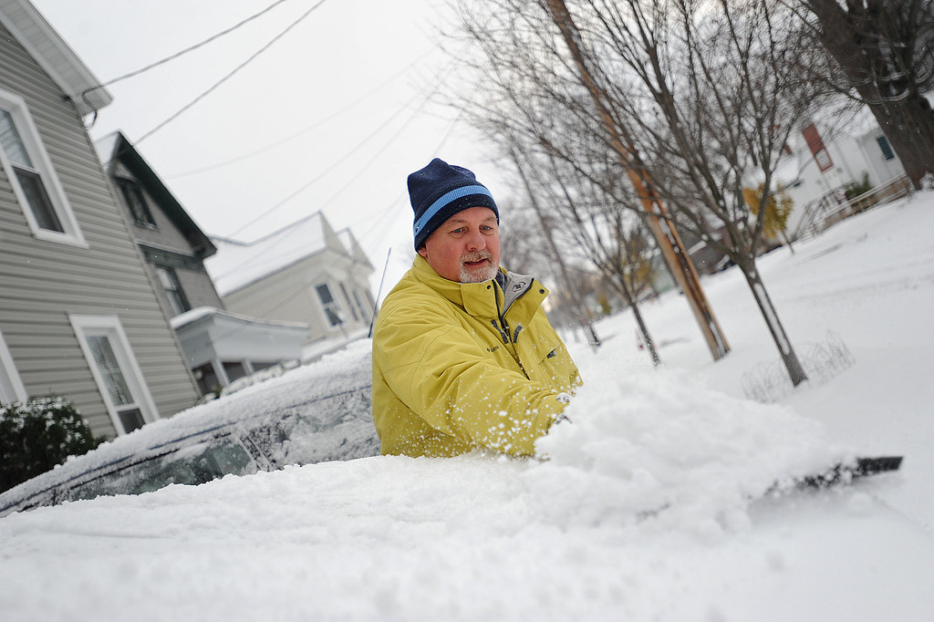 . In a Tuesday, Nov. 18, 2014 photo, Brian F. Miller clears snow off his wife\'s car on Boyd Street in Watertown, N.Y.  Before he finished his wife announced from the porch that she didn\'t have to go to work at the Jefferson County Courthouse due to weather.   A ferocious lake-effect storm left the Buffalo area buried under 6 feet of snow, trapping people on highways and in homes, and another storm expected to drop 2 to 3 feet more was on its way. (AP Photo/The Watertown Daily Times, Justin Sorensen)