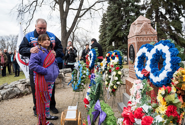President of the Manitoba Metis Federation David Chartrand along with his granddaughter Martha lay a copy of the historical framework agreement with the Government of Canada at Louis Riel's grave Wednesday November 16, 2016 during the Louis Riel Commemoration Ceremony at the St. Boniface Basilica Grounds. (David Lipnowski for Metro News)