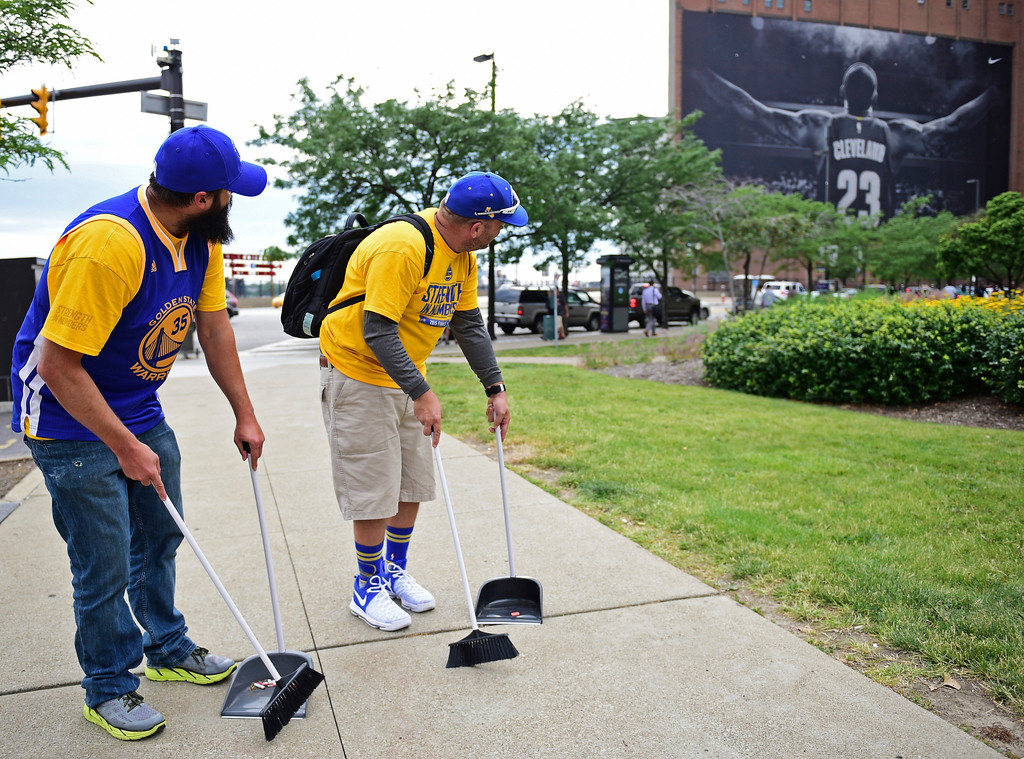 . Golden State Warrior fans Tom Harley, right, and David De Le Garza use brooms to indicate a potential sweep, while looking at a poster featuring Cleveland Cavaliers forward LeBron James before Game 4 of the basketball\'s NBA Finals between the Cavaliers and the Warriors, Friday, June 9, 2017, in Cleveland. (AP Photo/David Dermer)