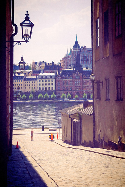 A woman takes pictures of the buildings around Riddarholmen Church. Manipulated in Photoshop to give it a painterly look.