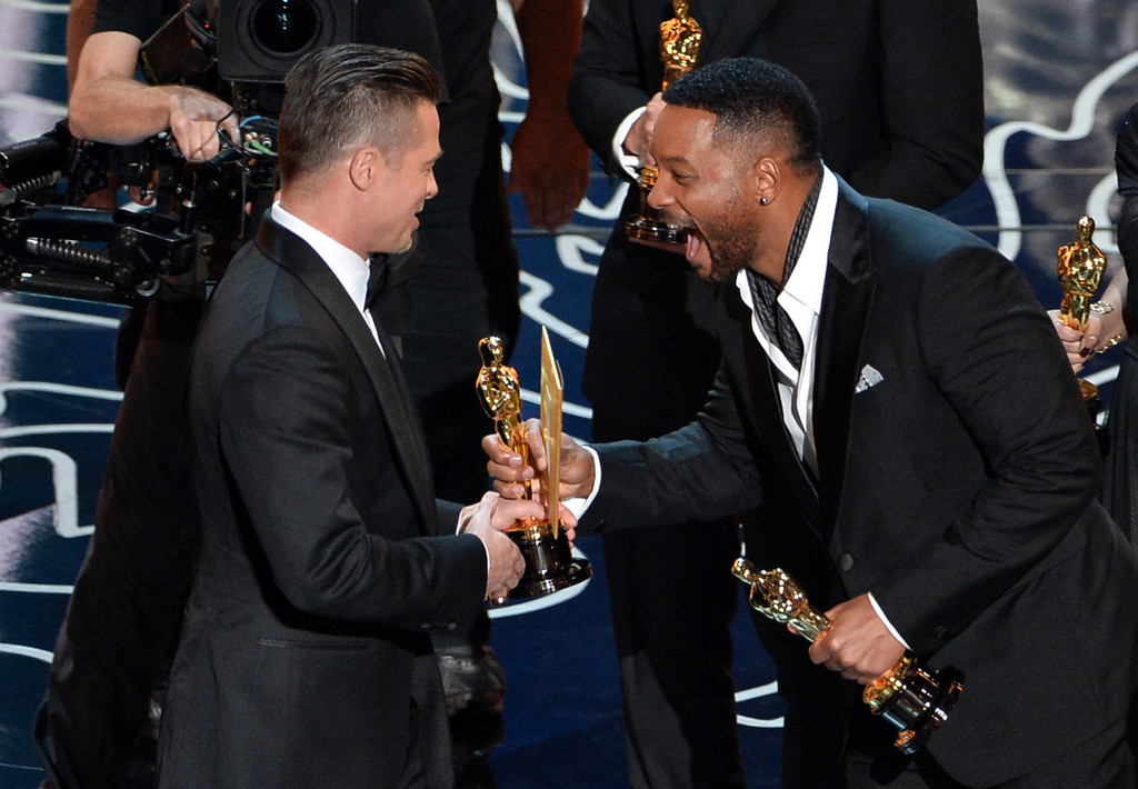 . Actor/producer Brad Pitt (L) accepts the Best Picture award for \'12 Years a Slave\' from actor Will Smith onstage during the Oscars at the Dolby Theatre on March 2, 2014 in Hollywood, California.  (Photo by Kevin Winter/Getty Images)