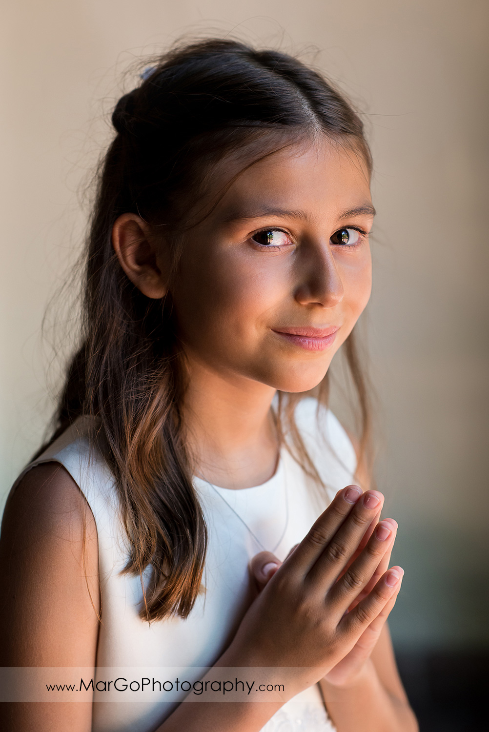 portrait of first communion girl in white dress with folded hands at Cafe Wisteria in Menlo Park