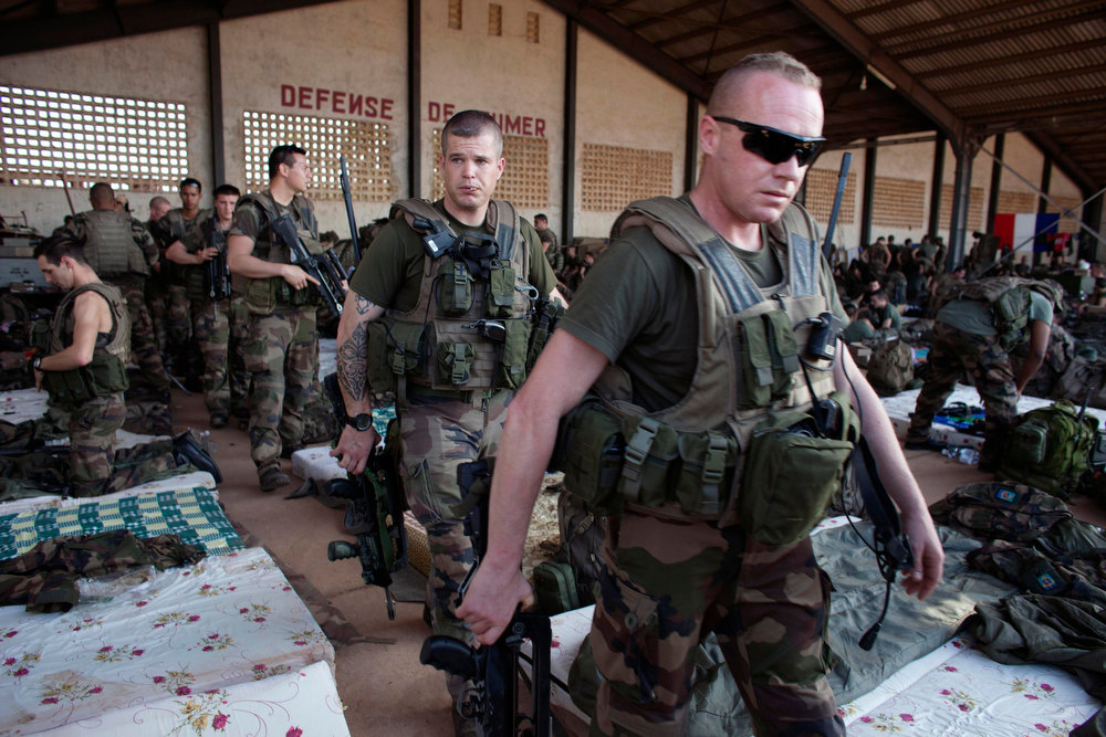 Description of . French soldiers leave a hangar at the Malian army air base in Bamako January 14, 2013. France, which has poured hundreds of troops into the capital Bamako in recent days, carried out more air raids on Monday in the vast desert area seized last year by an Islamist alliance grouping al Qaeda's north African wing AQIM alongside Mali's home-grown MUJWA and Ansar Dine militant groups. REUTERS/Joe Penney