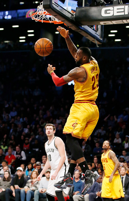 . Brooklyn Nets guard Sergey Karasev (10) and Cleveland Cavaliers guard J.R. Smith (5) watch from the floor as Cavaliers forward LeBron James (23) follows through on a backwards dunk in the first half of an NBA basketball game, Thursday, March 24, 2016, in New York. (AP Photo/Kathy Willens)
