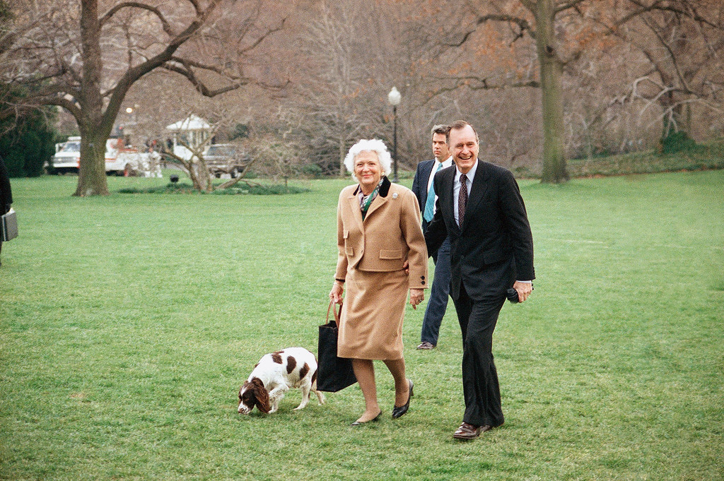 . U.S. President George H. and Mrs. Barbara Bush return to the White House in Washington, Sunday, March 12, 1989 from their weekend at Camp David. Their dog Millie, left, is expecting to give birth to puppies within a week or so. (AP Photo/Dennis Cook)
