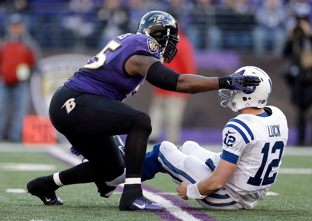 Description of . Baltimore Ravens outside linebacker Terrell Suggs (55) taps Indianapolis Colts quarterback Andrew Luck (12) on the helmet after a hit, during the second half of an NFL wild card playoff football game Sunday, Jan. 6, 2013, in Baltimore. (AP Photo/Patrick Semansky)