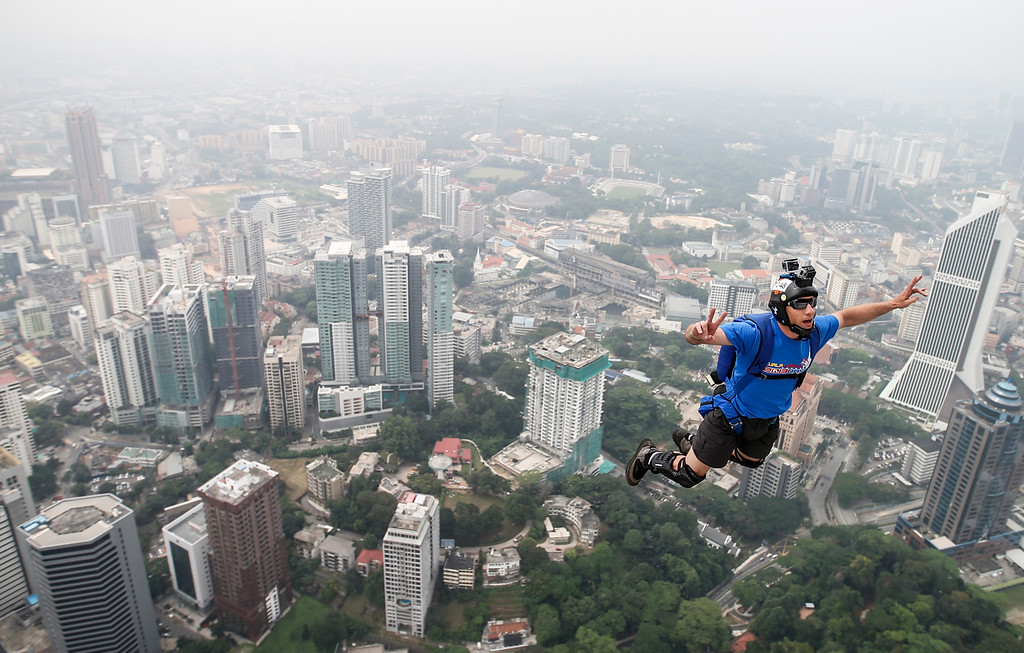 . Base jumper Kieran Francis Tomlinson of Australia\'s leaps from the 300-meter Open Deck of the Malaysia\'s landmark Kuala Lumpur Tower during the International Tower Jump in Kuala Lumpur, Friday, Sept. 27, 2013.  (AP Photo/Vincent Thian)