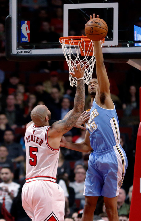 . Denver Nuggets forward Anthony Randolph (15) blocks the shot of Chicago Bulls forward Carlos Boozer (5) during the first half of an NBA basketball game Friday, Feb. 21, 2014, in Chicago. (AP Photo/Charles Rex Arbogast)