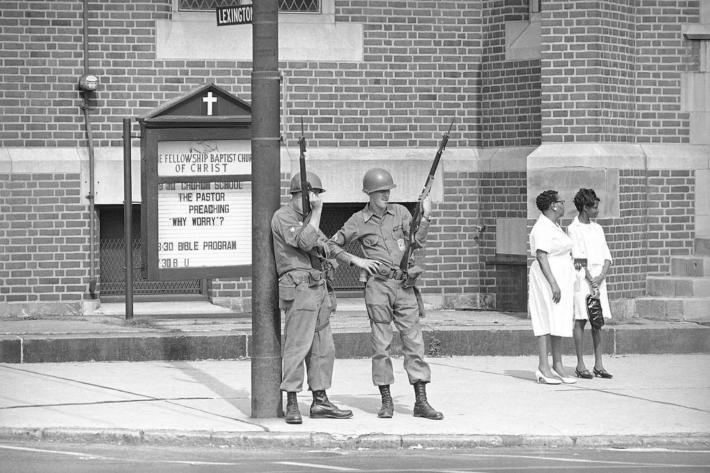 . There was plenty to worry about the past week, but today was peaceful after a quiet Saturday night, the first such since Monday when violence and vandalism rocked the Hough Avenue area of Cleveland. Here Sunday church-goers wait to enter church while to National Guardsmen stand at their post in Cleveland, Ohio, July 24, 1966. (AP Photo)