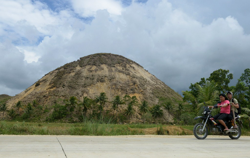 . Motorcycles pass by part of the World famous Chocolate Hills in Carmen, on October 17, 2013, the centre of the  7.1-magnitude earthquake that hit the central Philippine island of Bohol. Road access to the worst-hit towns on the central island of Bohol remained cut, two days after the 7.1-magnitude quake destroyed buildings and triggered landslides that engulfed homes and highways, regional civil defense chief Minda Morante said. AFP PHOTO/ Jay  DIRECTO/AFP/Getty Images