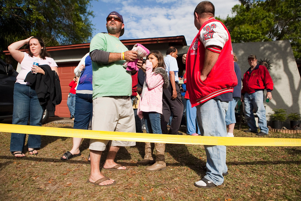 . A crowd gathers at the home of Jeff Bush after he was consumed by a sinkhole while lying in bed last night, March 1, 2013 in Seffner, Florida.  (Photo by Edward Linsmier/Getty Images)