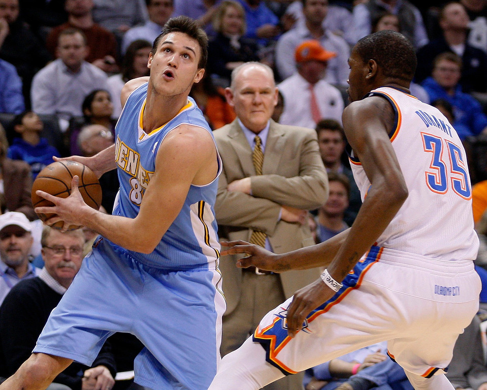 . Denver Nuggets\' Danilo Gallinari (8) of Italy, drives against Oklahoma City Thunder forward Kevin Durant (R) as Nuggets head coach George Karl (C) watches from the sideline in the first half of their NBA basketball game in Oklahoma City, Oklahoma January 16, 2013. REUTERS/Bill Waugh