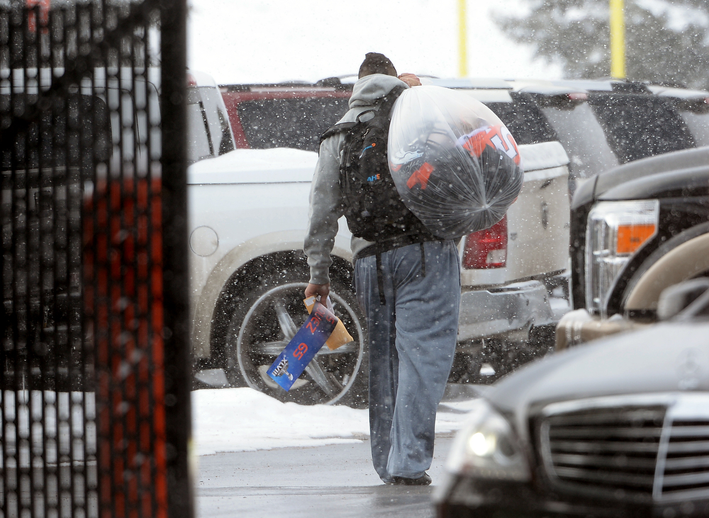 . Denver Broncos guard Louis Vasquez carries a bag of belongings as well as the Super Bowl name plate from the game to his car as he and other players leave Dove Valley for the season  in Englewood, Co on February 4, 2014. (Photo By Helen H. Richardson/ The Denver Post)