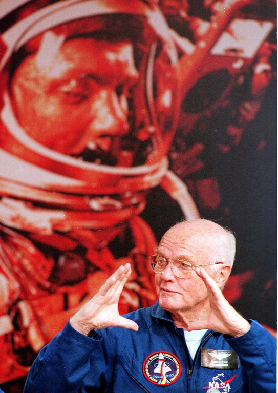 . Space shuttle Discovery astronaut Sen. John Glenn, D-Ohio, gestures during a news conference at the Kennedy Space Center on Sunday, Nov. 8, 1998, in front of a 1962 picture of himself from his previous stint as an astronaut. Glenn and six other astronauts completed their nine-day mission on Saturday and will fly back to Houston on Sunday to begin analyzing data from the experiments they had on board. (AP Photo/Terry Renna)
