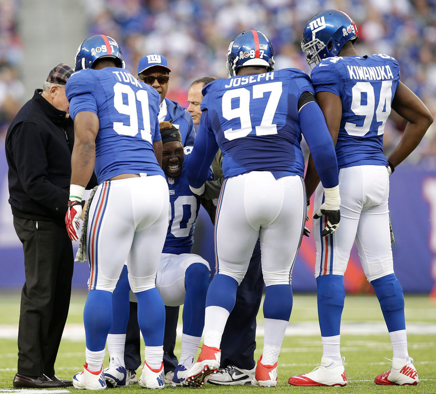 . New York Giants defensive end Jason Pierre-Paul, center, is helped up by teammates during the first half of an NFL football game against the Oakland Raiders, Sunday, Nov. 10, 2013, in East Rutherford, N.J. (AP Photo/Kathy Willens)