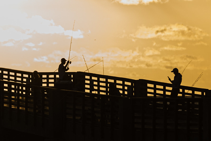 The rising sun silhouettes people fishing from the William O. Lockhart Pier in Lake Worth Beach, Tuesday, October 27, 2020. (JOSEPH FORZANO / THE PALM BEACH POST)