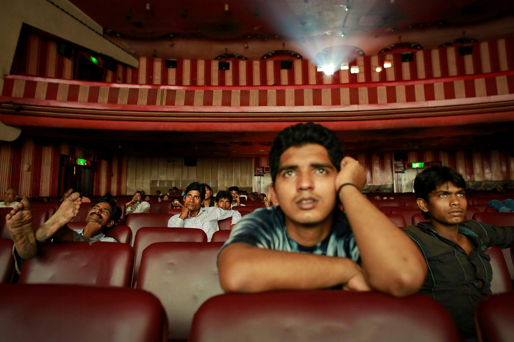 """. Ram Pratap Verma, a 32-year-old aspiring Bollywood film actor, watches a film at a cinema in Mumbai May 2, 2013. Bollywood is an addiction for many; an addiction that attracts thousands of aspiring stars to the city of Mumbai. Ram Pratap Verma made the journey from his small village eight years ago, and despite carrying his whole \""""home\"""" inside his bag, he is determined not to give up on his ambitions. He endeavours to watch at least one film a week at a cinema, where the silver screen keeps his dreams alive. Picture taken May 2, 2013. REUTERS/Danish Siddiqui"""