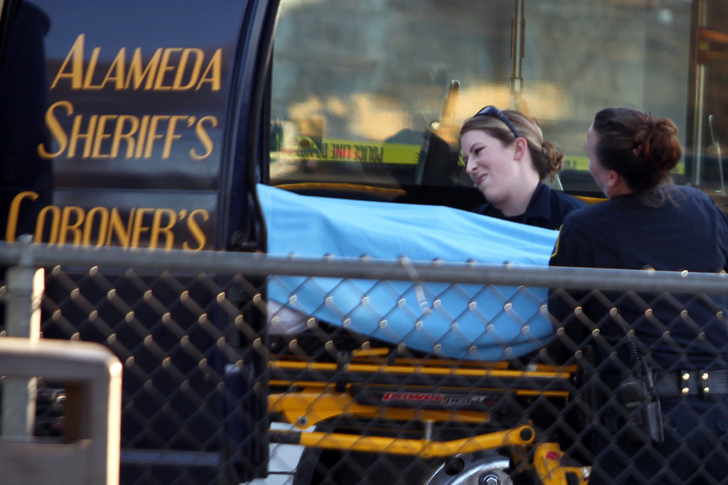 . Officers from the Alameda County Sheriff\'s Office Coroner\'s Burea take away a body as police investigate the fatal shooting in the bus yard outside the Bay Fair BART station in San Leandro, Calif., on Saturday, Jan. 19, 2013. (Ray Chavez/Staff)