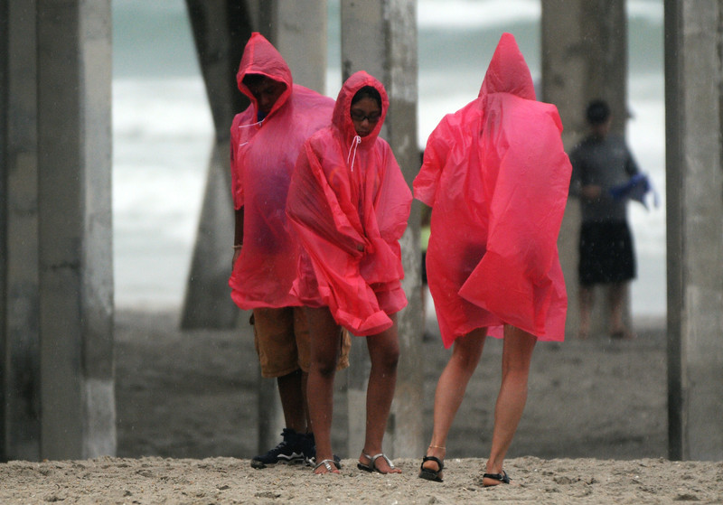. Beach goers huddle on the beach at Wrightsville Beach, N.C., Thursday, July 3, 2014. Residents along the coast of North Carolina are bracing for the arrival of the Hurricane Arthur, a category one storm. (AP Photo/Wilmington Star-News, Mike Spencer)