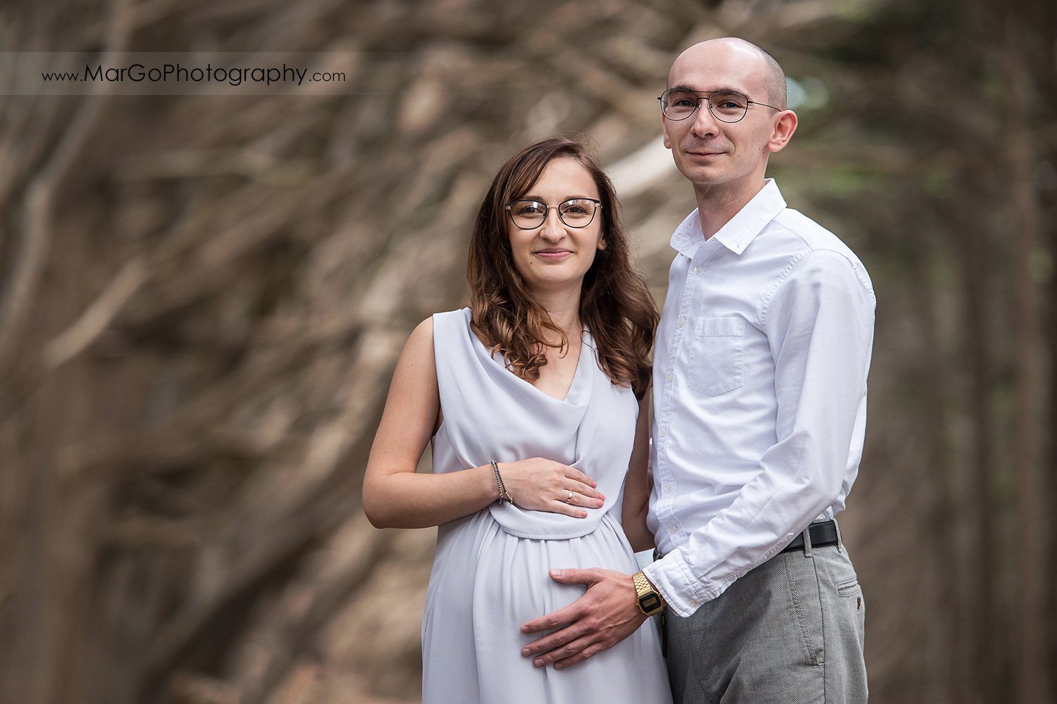portrait of man and pregnant woman in long gray dress during Seal Cove Cypress Tree Tunnel maternity session