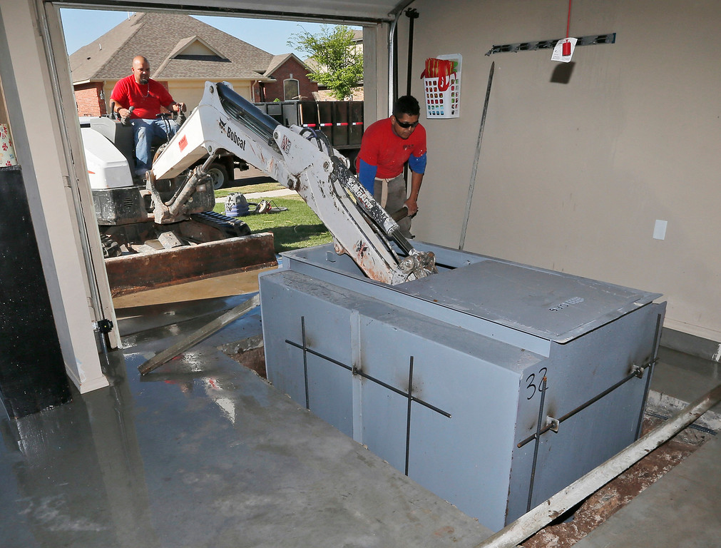 . In this Friday, May 2, 2014 photo, Art Munoz, of GFS Storm Shelters, lowers a storm shelter into a hole dug through the slab in a garage as Vic Rodriguez assists him at a residence in Yukon, Okla. (AP Photo/Sue Ogrocki)