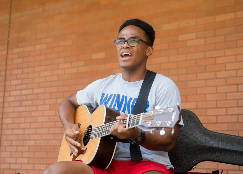 Student Antony Lametrie plays his guitar in the Center for Instruction courtyard between classes.