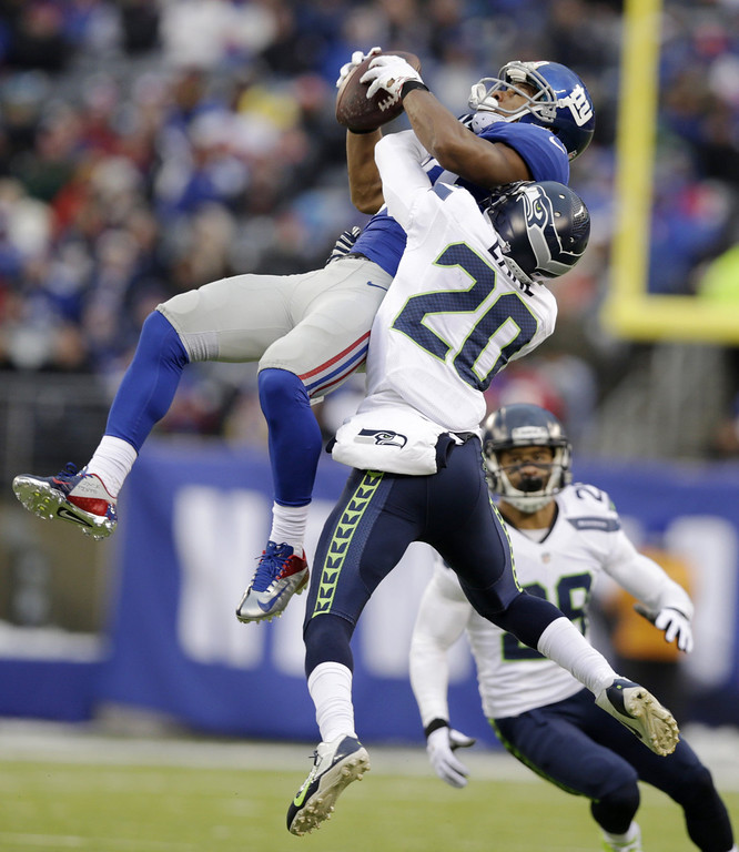 . New York Giants wide receiver Victor Cruz, left, makes a catch as Seattle Seahawks cornerback Jeremy Lane defends on the play during the second half of an NFL football game, Sunday, Dec. 15, 2013, in East Rutherford, N.J. Cruz was banged up on the play and left the game with an injury. (AP Photo/Kathy Willens)
