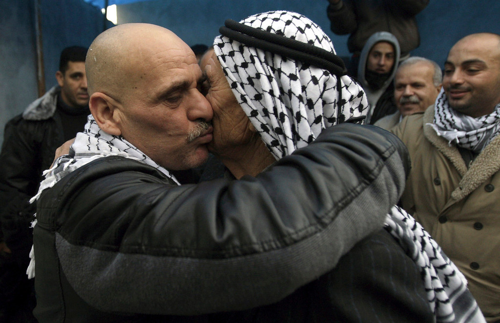 . Palestinian released prisoner Ahmad Kmail, left,  kisses his father after arriving at his home in the West Bank village of Kabatyeh near Jenin, Tuesday, Dec. 31, 2013. Kmail is one of more than two dozen Palestinian prisoners convicted in deadly attacks against Israelis early Tuesday, released by Israel, as part of a U.S.-brokered package to restart Mideast peace talks. (AP Photo/Mohammed Ballas)