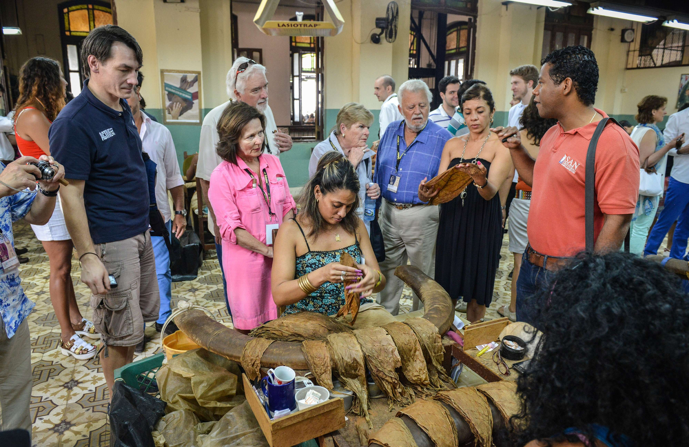 . Tourists watch as a worker makes cigars cigars, on February 27, 2014 during a guided visit to the H. Upmann cigar factory in Havana. The production of Cuban cigars experienced an 8% growth in 2013 adding 447 million dollars to the Cuban economy. The XVI Havana Cigar Festival is running in Cuba with the presentation of the best Cuban cigars. (ALBERTO ROQUE/AFP/Getty Images)