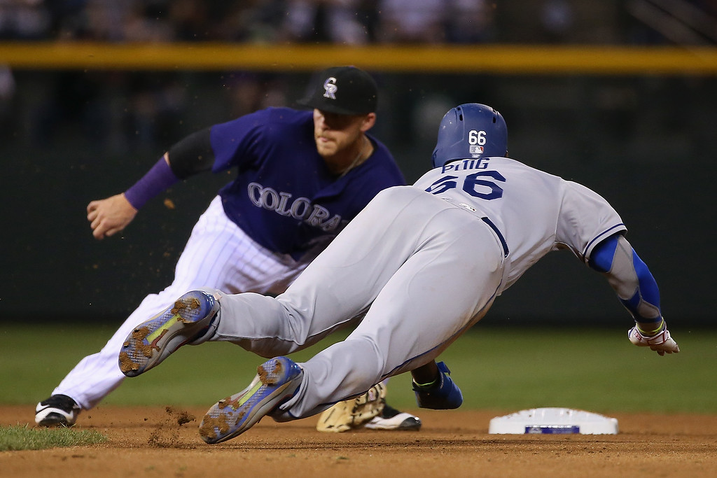 . DENVER, CO - APRIL 22:  Yasiel Puig #66 of the Los Angeles Dodgers dives into second with a stolen base as shortstop Trevor Story #27 of the Colorado Rockies fails to catch the throw allowing Puig to advance to third in the fourth inning at Coors Field on April 22, 2016 in Denver, Colorado. (Photo by Doug Pensinger/Getty Images)
