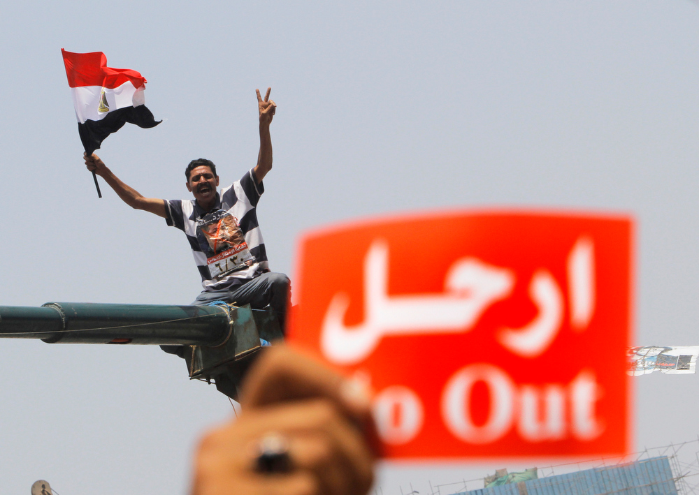 ". An opponent of Egypt\'s Islamist President Mohammed Morsi shouts slogans during a protest in Tahrir Square in Cairo, Egypt, Wednesday, July 3, 2013. A Defense Ministry official said army chief Gen. Abdel-Fattah el-Sissi is meeting with his top commanders, hours before the military\'s deadline to the president and opposition to resolve the nation\'s political crisis is set to expire. Arabic read "" leave.\""  (AP Photo/Amr Nabil)"