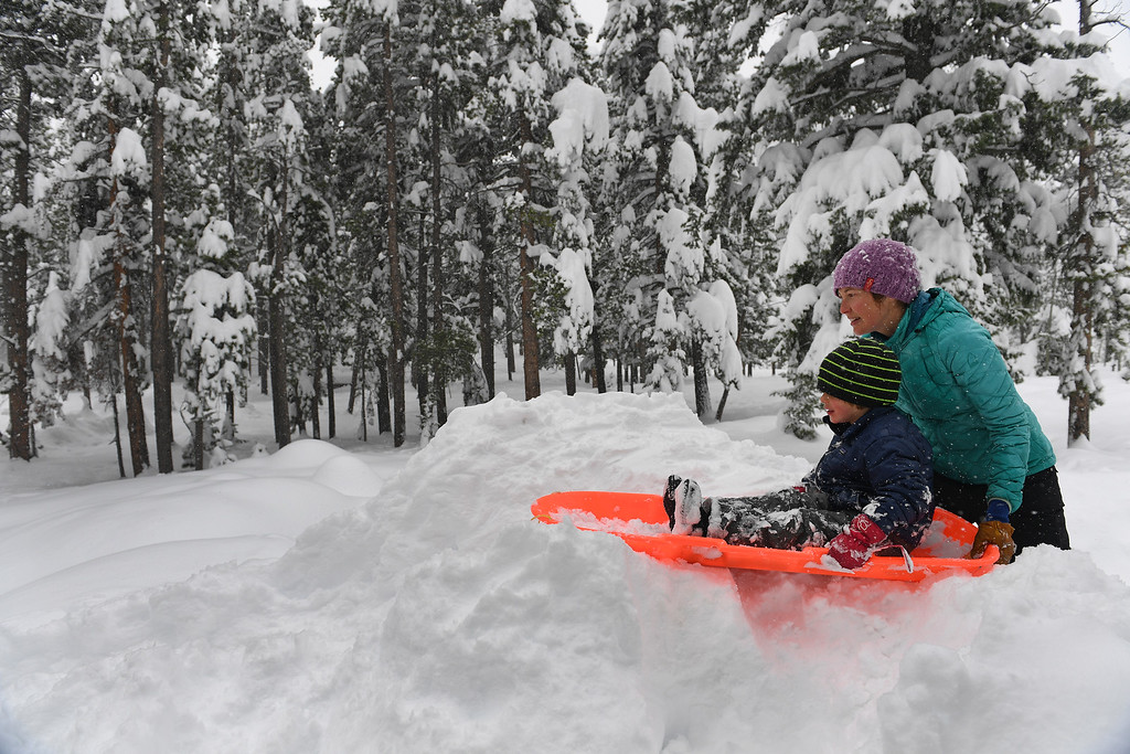 . NEDERLAND, CO - APRIL 17: Brynel Dodge pushes her son Wyatt, 4, on his sled on a small hill in their driveway on April 17, 2016 in Nederland, Colorado. A slow moving spring storm dumped almost 3 feet of snow in the foothills. Over 35 inches of snow fell in the area over a two day period. (Photo by Helen H. Richardson/The Denver Post)