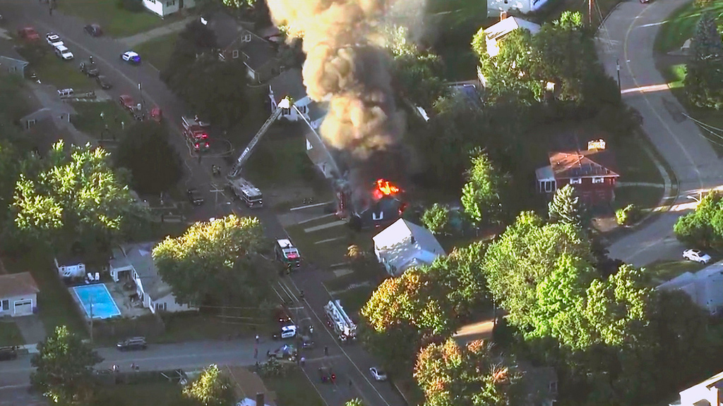 . In this image take from video provided by WCVB in Boston, firefighters battle a raging house fire in Lawrence, Mass, a suburb of Boston, Thursday, Sept. 13, 2018. Emergency crews responded to what they believe is a series of gas explosions that have damaged homes across three communities north of Boston. (WCVB via AP)