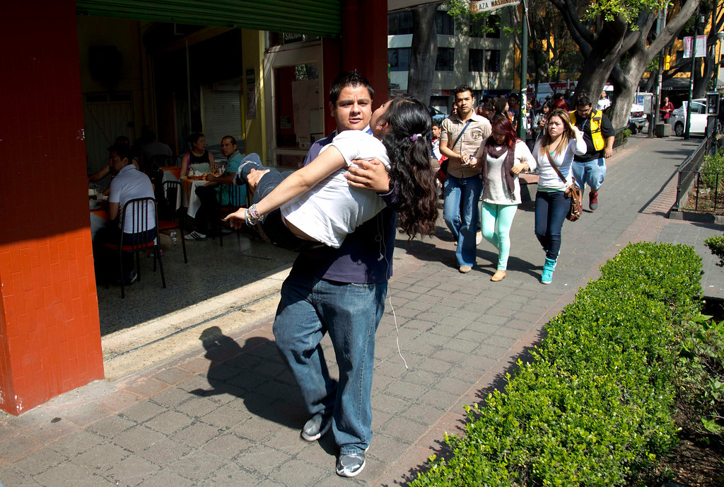 . A woman is carried at the Juarez neighborhood after a strong earthquake jolted Mexico City, Friday, April 18, 2014. The powerful magnitude-7.2 earthquake shook central and southern Mexico but there were no early reports of major damage or casualties. (AP Photo/Eduardo Verdugo)