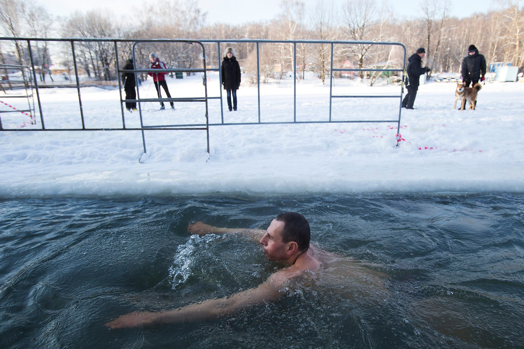 . A man swims in the ice cold water to mark Epiphany in Moscow, Russia, Saturday, Jan. 18, 2014. The temperature in Moscow is -13C ( -8.6 F). Thousands of Russian Orthodox Church followers plunged into icy rivers and ponds across the country to mark Epiphany, cleansing themselves with water deemed holy for the day. Water that is blessed by a cleric on Epiphany is considered holy and pure until next year\'s celebration, and is believed to have special powers of protection and healing. (AP Photo/Pavel Golovkin)