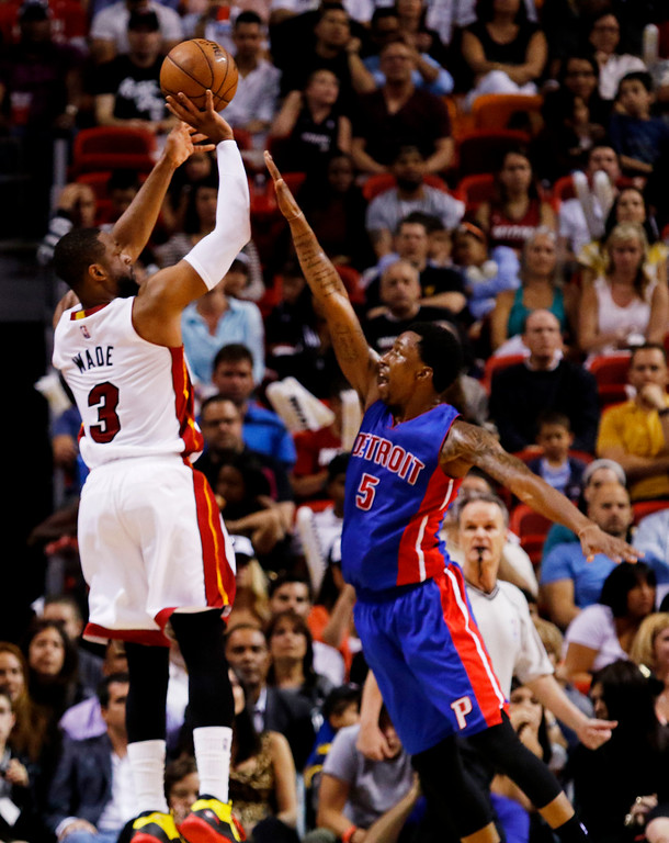 . Miami Heat guard Dwyane Wade (3) shoots over guard Kentavious Caldwell-Pope in the second half of an NBA basketball game, Sunday, March 29, 2015, in Miami. (AP Photo/Joe Skipper)