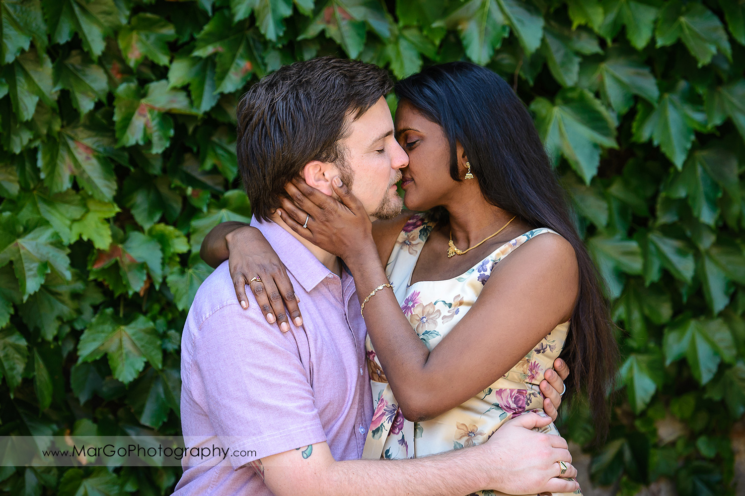 man in pink shirt and Indian woman in flower dress kissing on green background during engagement session at Castello di Amorosa in Calistoga