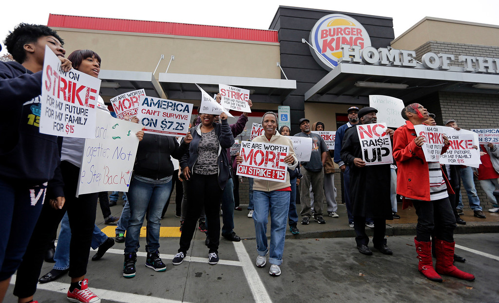 . Protestors chant outside a Burger King restaurant during a protest for a raise in the minimum wage in Charlotte, N.C., Thursday, Dec. 5, 2013. Fast food workers across the country walked off their jobs to fight for a $15 an hour wage. (AP Photo/Chuck Burton)